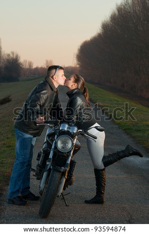 Attractive young couple kissing over the motorcycle at beautiful autumn sunset. - stock photo