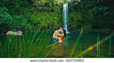 Attractive young couple kissing under jungle waterfall