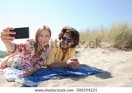 Attractive young couple laying together on a beach on a summer holiday using a smartphone mobile to take selfies pictures of themselves, outdoors. Travel technology lifestyle, nature exterior. - stock photo