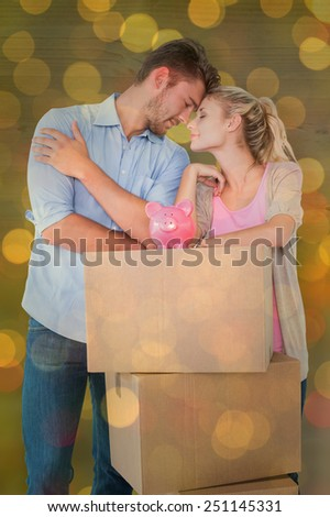 Attractive young couple leaning on boxes with piggy bank against close up of christmas lights - stock photo