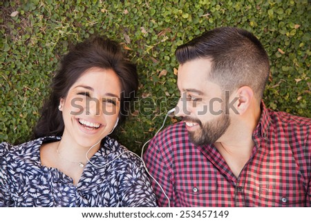 Attractive young couple listening to music and having fun together at a park - stock photo
