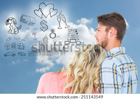 Attractive young couple looking together against cloudy sky - stock photo