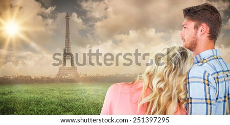 Attractive young couple looking together against paris under cloudy sky - stock photo