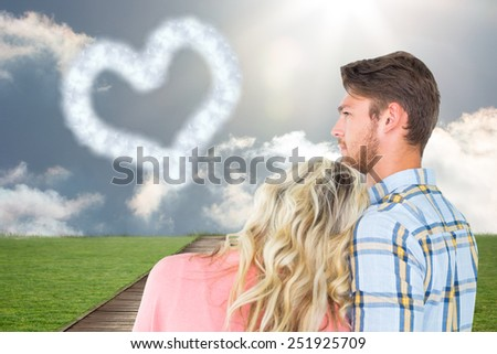 Attractive young couple looking together against path on grass - stock photo
