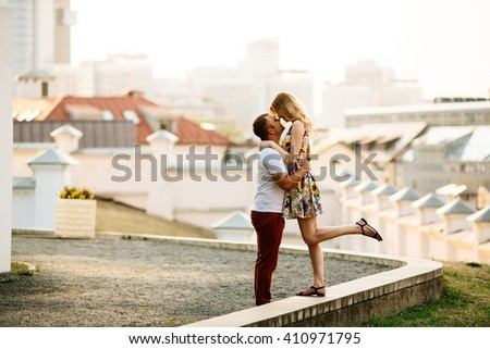 Attractive young couple lovely hugging in the city and looking each other. Photo with copy space at sunny day - stock photo