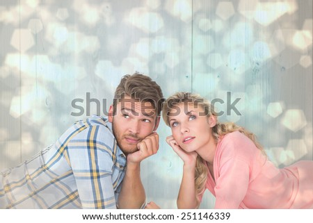 Attractive young couple lying and thinking against light glowing dots design pattern - stock photo
