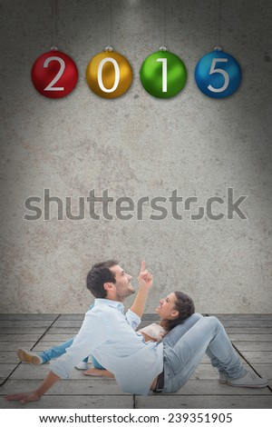 Attractive young couple lying down against grey room - stock photo