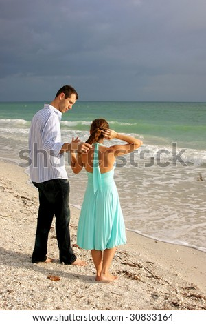 attractive young couple on beach in florida having a discussion with waves crashing in front of them. she is fixing her hair, he appears to be listening - stock photo