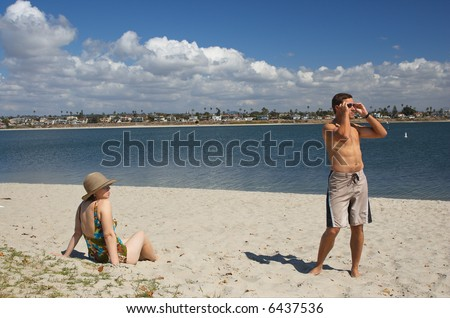 Attractive young couple on the beach looking at an object of interest off camera. - stock photo
