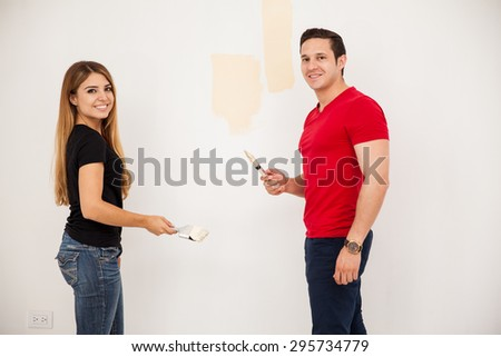 Attractive young couple painting a room in their new apartment and smiling