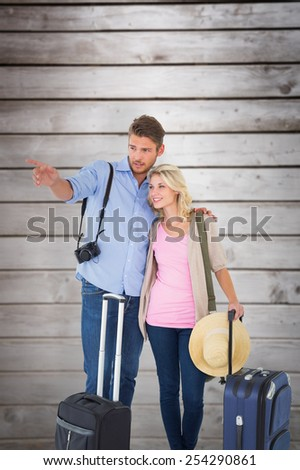 Attractive young couple ready to go on vacation against wooden planks - stock photo