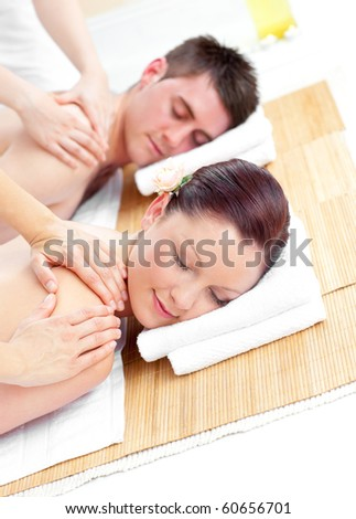 Attractive young couple receiving a back massage in a spa center - stock photo