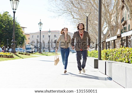 Attractive young couple running together in a destination vacation city, holding hands and smiling.