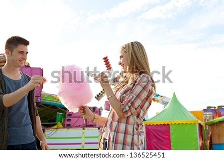 Attractive young couple sharing a pink cotton candy floss sweet wile enjoying a funfair ground with colorful rides and a blue sky, smiling. - stock photo