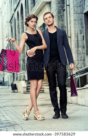 Attractive young couple shopping in the city. Seasonal sale. Fashion shot.