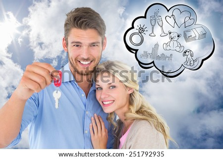 Attractive young couple showing new house key against bright blue sky with clouds - stock photo