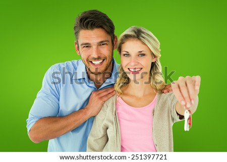 Attractive young couple showing new house key against green vignette - stock photo