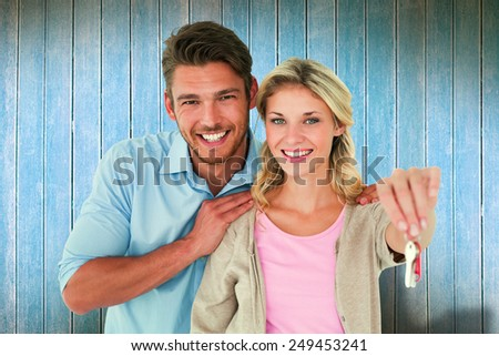 Attractive young couple showing new house key against wooden planks - stock photo