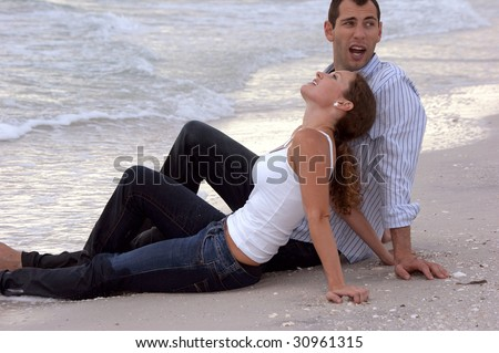 Attractive young couple sitting at the water fully dressed at the beach having a conversation on an overcast day. - stock photo