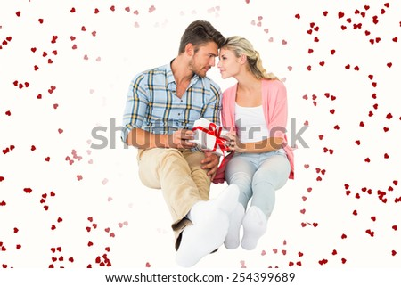 Attractive young couple sitting holding a gift against red love hearts - stock photo