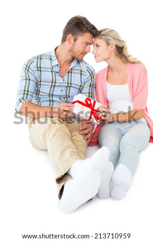 Attractive young couple sitting holding a gift on white background - stock photo