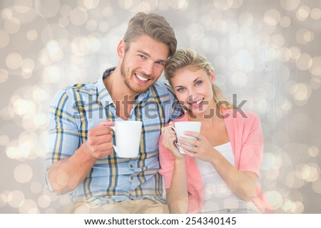 Attractive young couple sitting holding mugs against light glowing dots design pattern - stock photo
