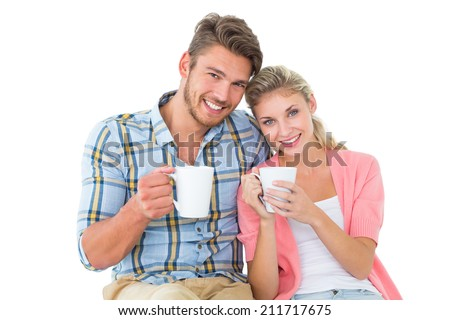 Attractive young couple sitting holding mugs on white background - stock photo