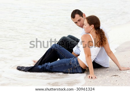 Attractive young couple sitting in the water fully dressed at the beach having a conversation. - stock photo