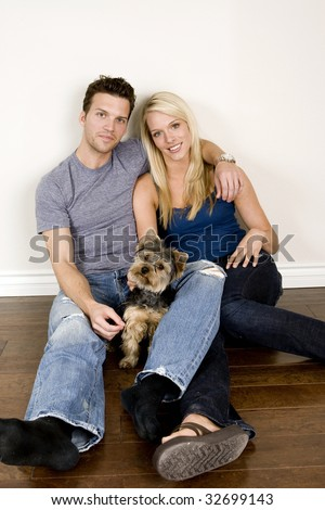 Attractive young couple sitting in their new home with their dog - stock photo