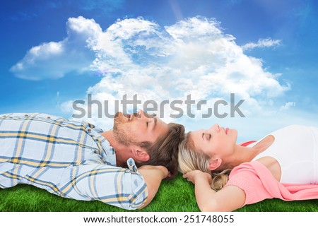 Attractive young couple sleeping peacefully against cloud heart - stock photo