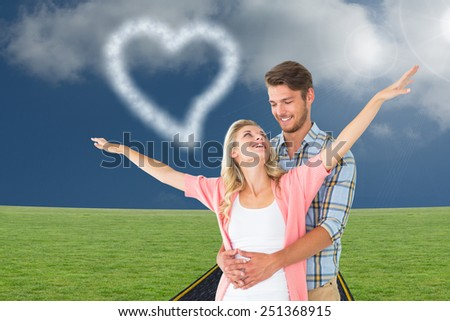 Attractive young couple smiling and embracing against road on grass - stock photo