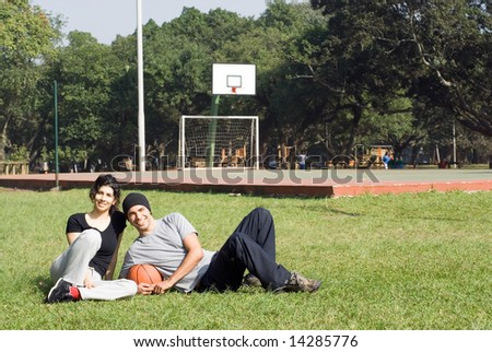 Attractive young couple smiling and laying together on the grass in a a park.  The man is holding a basketball.  Horizontally framed shot. - stock photo