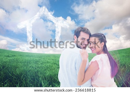 Attractive young couple smiling at camera against green field under blue sky - stock photo