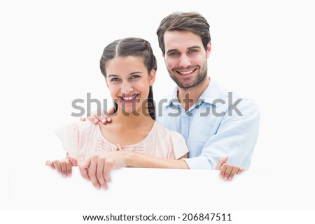 Attractive young couple smiling at camera on white background - stock photo