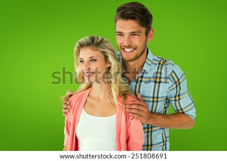 Attractive young couple smiling together against green vignette - stock photo