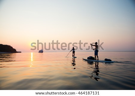 Attractive Young couple Stand Up Paddle Boarding, active beach lifestyle