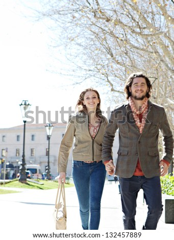 Attractive young couple walking fast together in a destination vacation city, holding hands and smiling. - stock photo