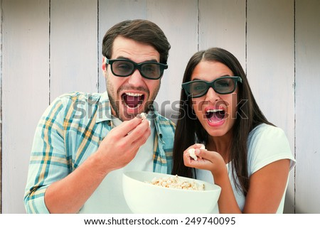 Attractive young couple watching a 3d movie against wooden planks - stock photo