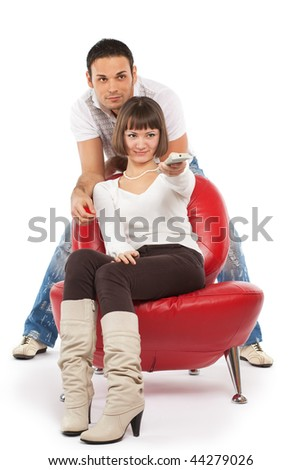 Attractive young couple watching TV; isolated on white - stock photo