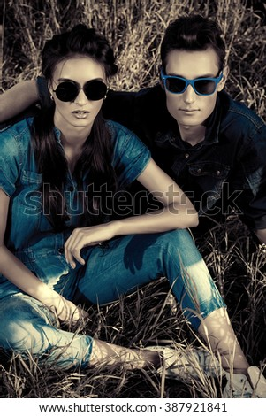 Attractive young couple wearing jeans clothes lying relaxed on a grass. Fashion shot. - stock photo