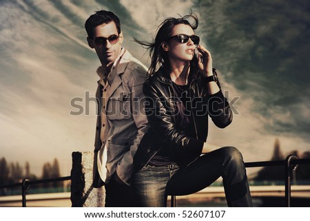Attractive young couple wearing sunglasses - stock photo
