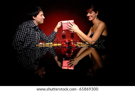 Attractive young couple with a gift in hands - stock photo