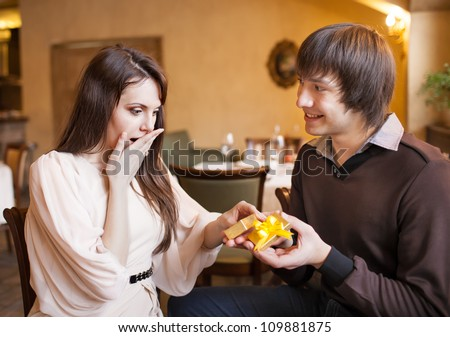 Attractive young couple with a gift in hands at restaurant - stock photo