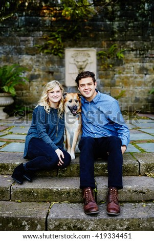 Attractive Young Couple with Dog sitting down smiling at camera in park
