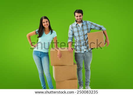 Attractive young couple with moving boxes against green vignette - stock photo