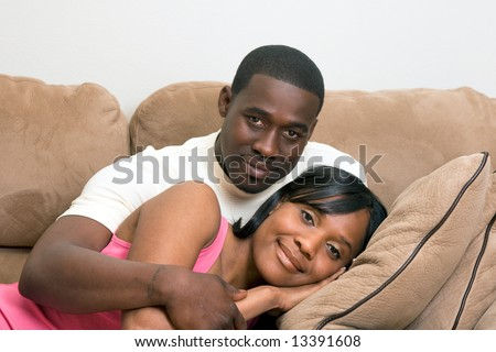 Attractive young couple, with neutral expressions, relaxing on a sofa.  The man is sitting, and the woman lying with her head in his lap.  Horizontally framed close-up shot. - stock photo