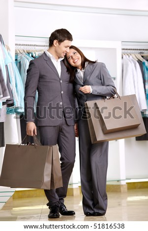Attractive young couple with purchases in shop - stock photo