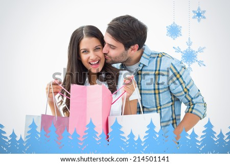 Attractive young couple with shopping bags against snowflakes and fir trees in blue - stock photo