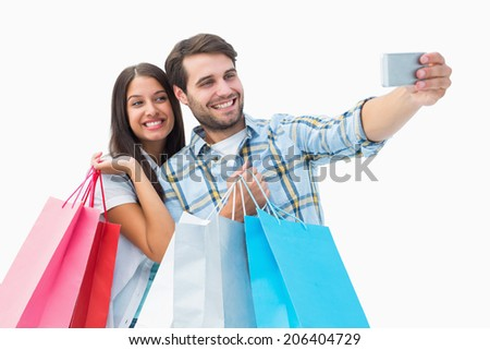 Attractive young couple with shopping bags taking a selfie on white background - stock photo