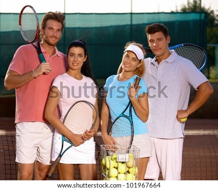 Attractive young couples standing on tennis court, smiling, looking at camera.